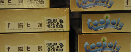 Stacks of Co-opoly boxes waiting to hit the social justice assembly line