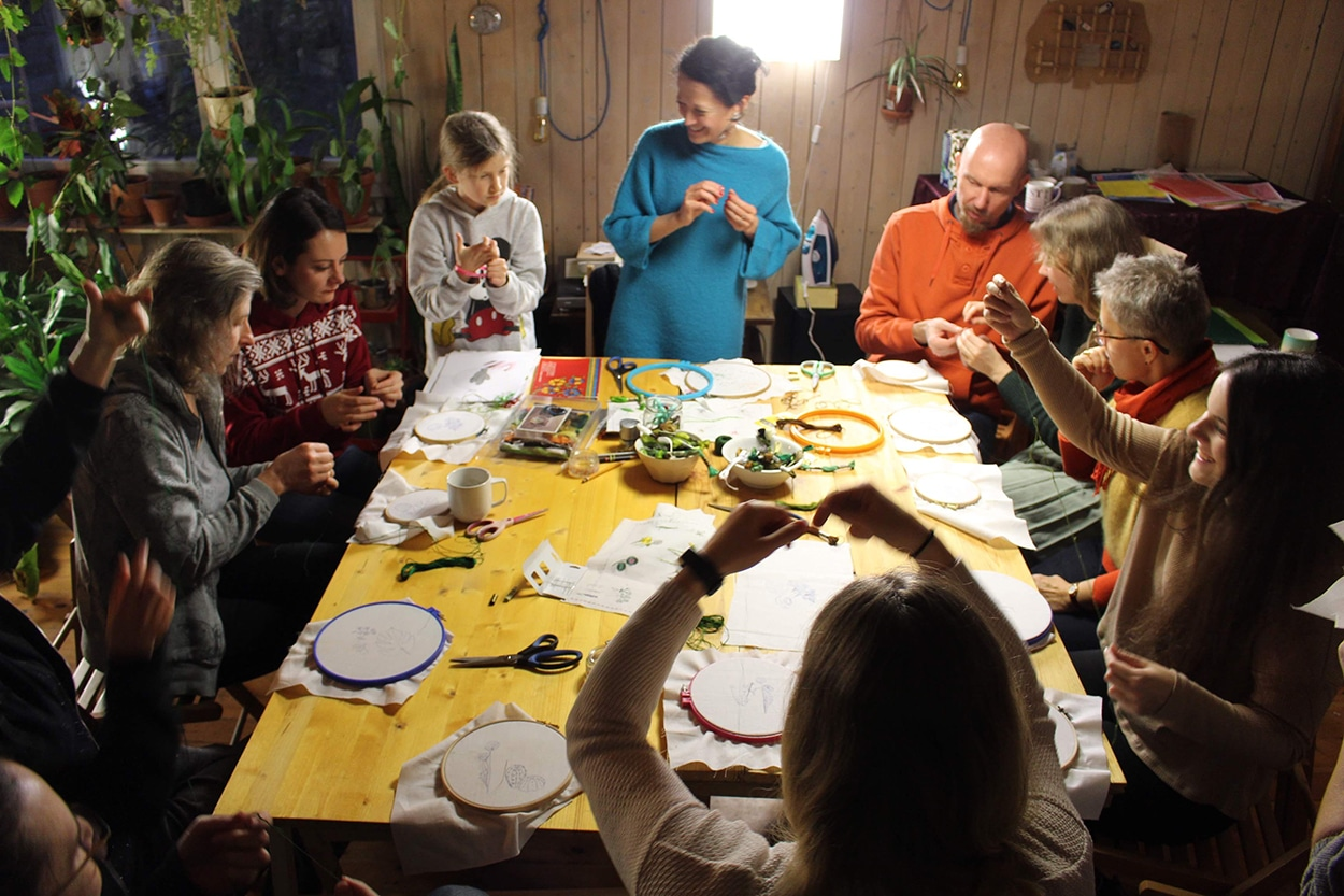 group of people sitting around a table doing crafts