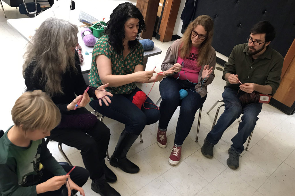 group of people learning to crochet