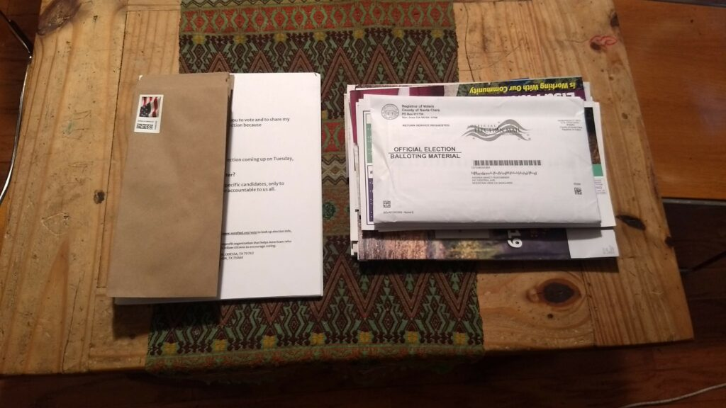On the left is a stack of letters to voters in Florida and Texas waiting for me to write and mail as part of a get out the vote campaign. On the right is our ballots and a huge stack of mailers from candidates, the most we've ever received. Photo: Neal Gorenflo