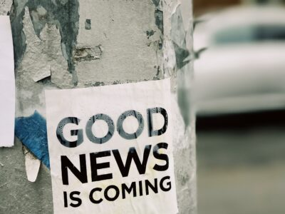 "Photo of a sign posted to a tree stating ""good news is coming"""