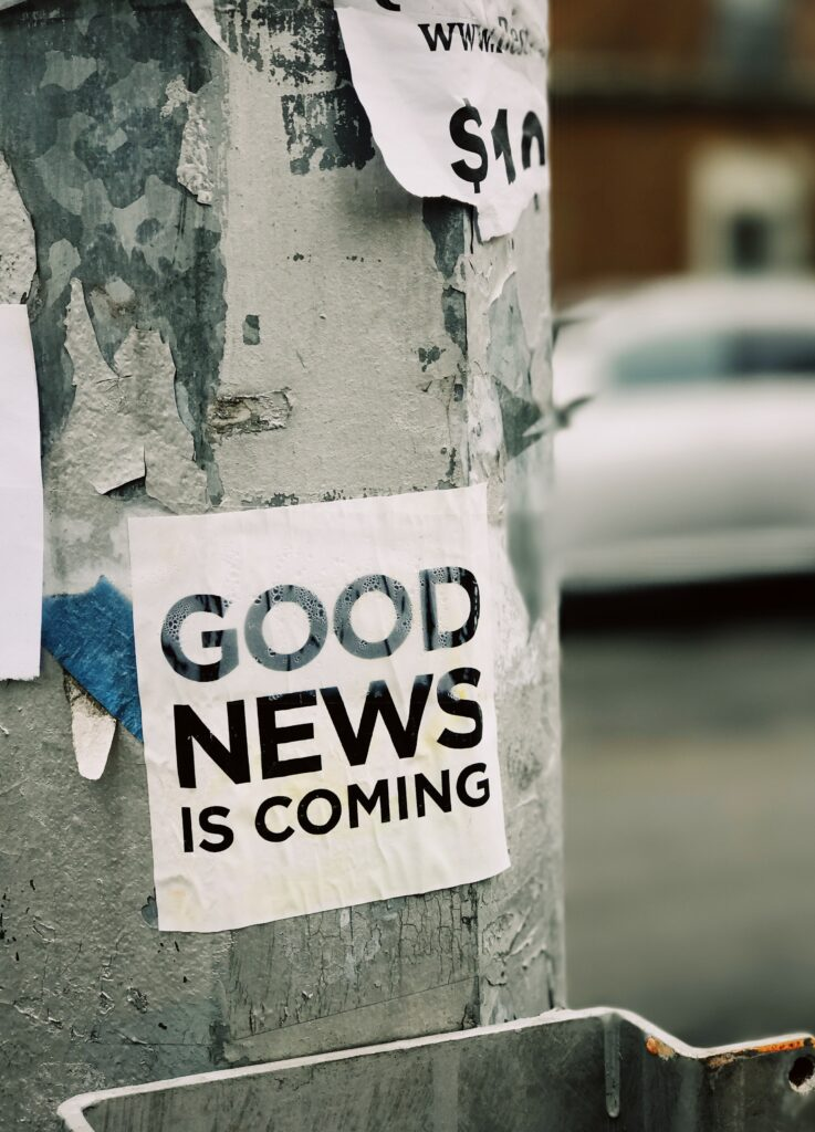 """Photo of a sign posted to a tree stating """"good news is coming"""""""