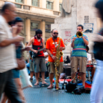 Musicians playing on a busy city street.