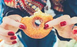 Image of a hand holding a doughnut