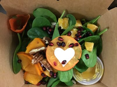 salad in a take out box with heart shaped produce cutout