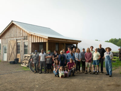 large group of farmers standing in front of a barn
