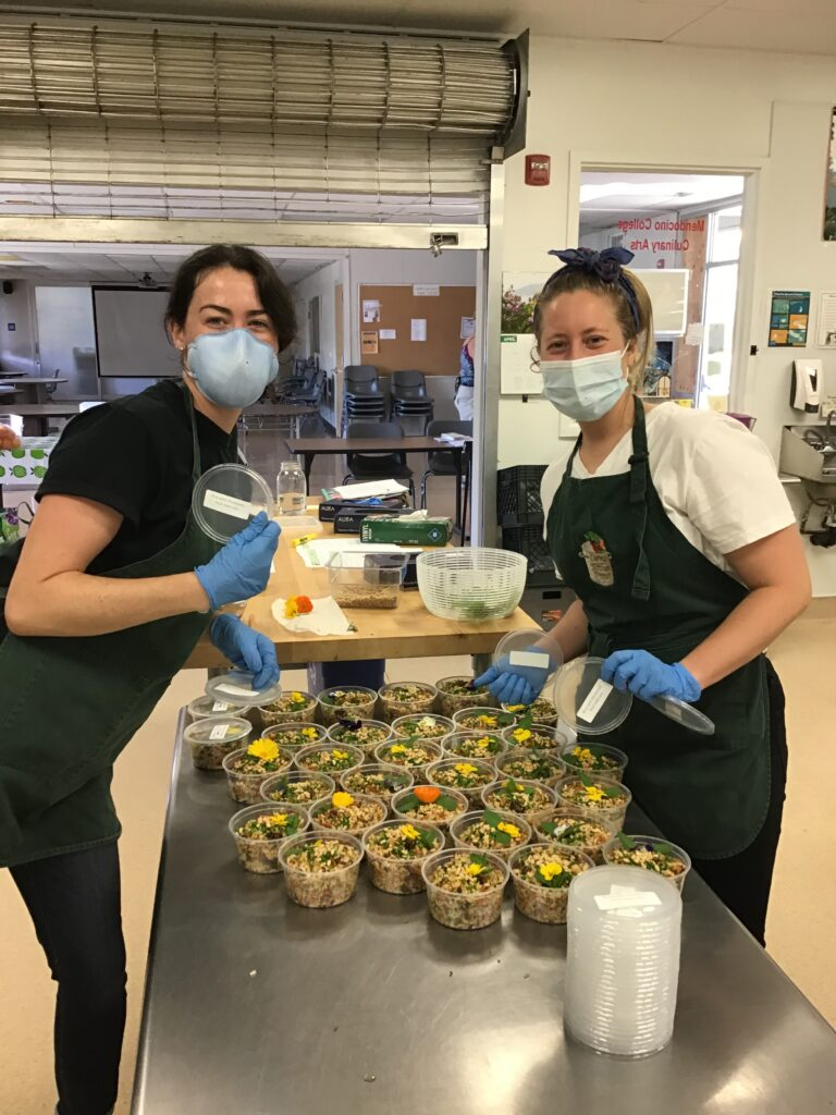 two volunteers prepare local food in kitchen wearing face masks