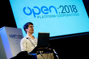 """Oliver Sylvester-Bradley speaking at a conference with a laptop in front of a large screen that reads """"OPEN 2018"""""""