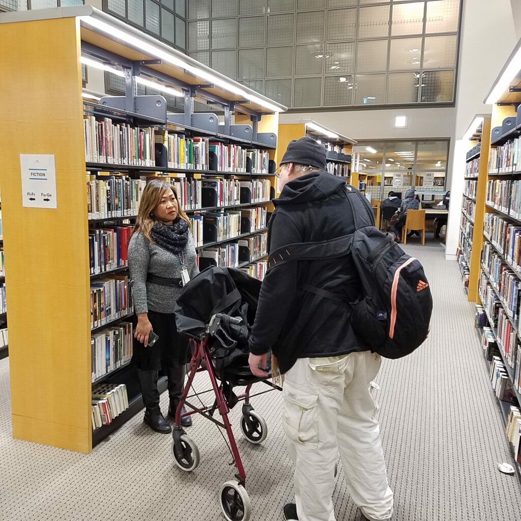 Photo of librarian speaking with a houseles individual in front of library book shelves