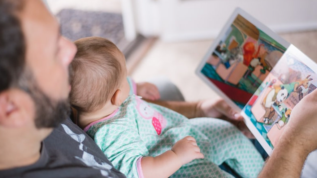 Photo of a father reading a book to a small infant being held in his arms