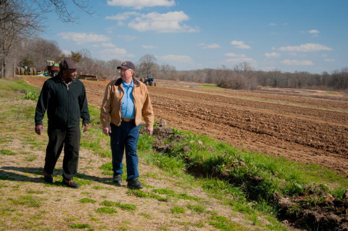 Charlie Williams (left), United States Department of Agriculture, Arkansas Strike Team Leader and Bill Hess walk along a side a pasture sharing a conversation