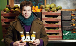 Man wearing a scarf stands in front of wooden food bin holding three bottles of fresh made juices