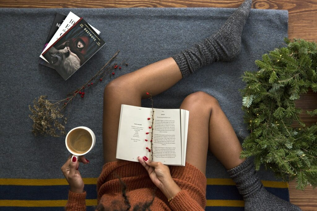 Woman sits reading books wearing cozy socks and with a cup of coffee in hand