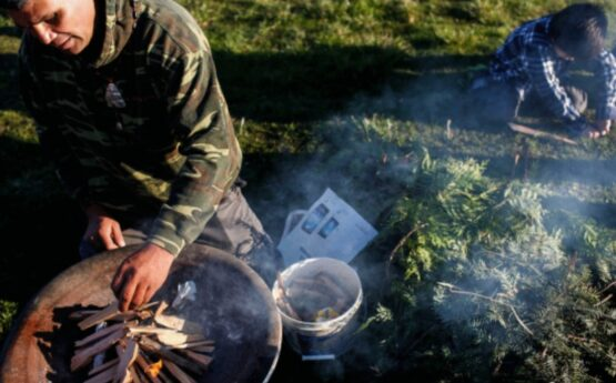 A Wiyot man tends a fire in preparation of the candlelight vigil remembrance ceremony.