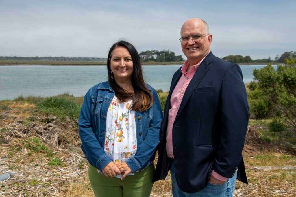 Photo of Wiyot Tribal Administrator Michelle Vassel and Cooperation Humboldt Co-founder and Executive Director David Cobb, with Tuluwat Island in the background.