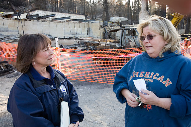 Community relations worker speaks with resident in California following a wildfire Credit: WikiCommons