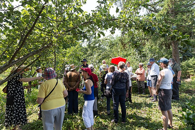 members of a community orchard gather for a viewing and small tour meeting
